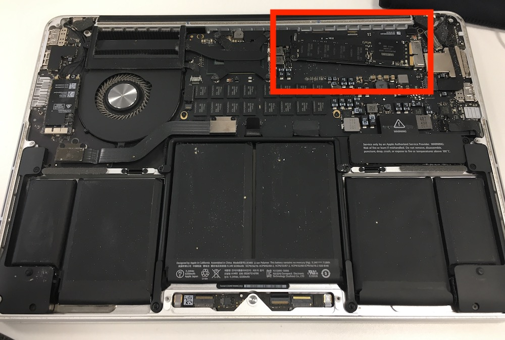 MacBook Pro 13 2014 model with back panel opened, showing SSD under funny angle