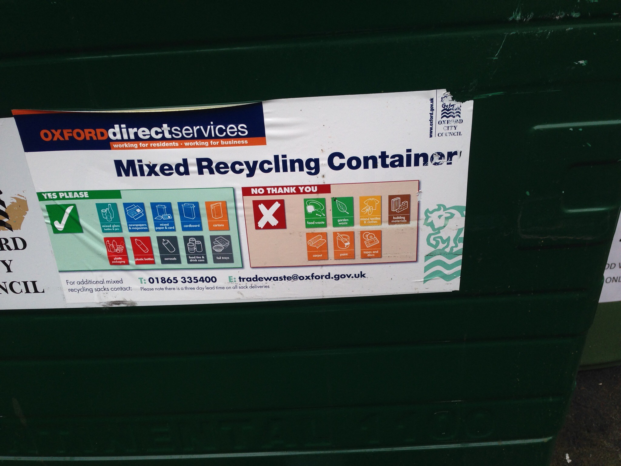 Black rectangular bin with a sticker that shows whats recyclable.